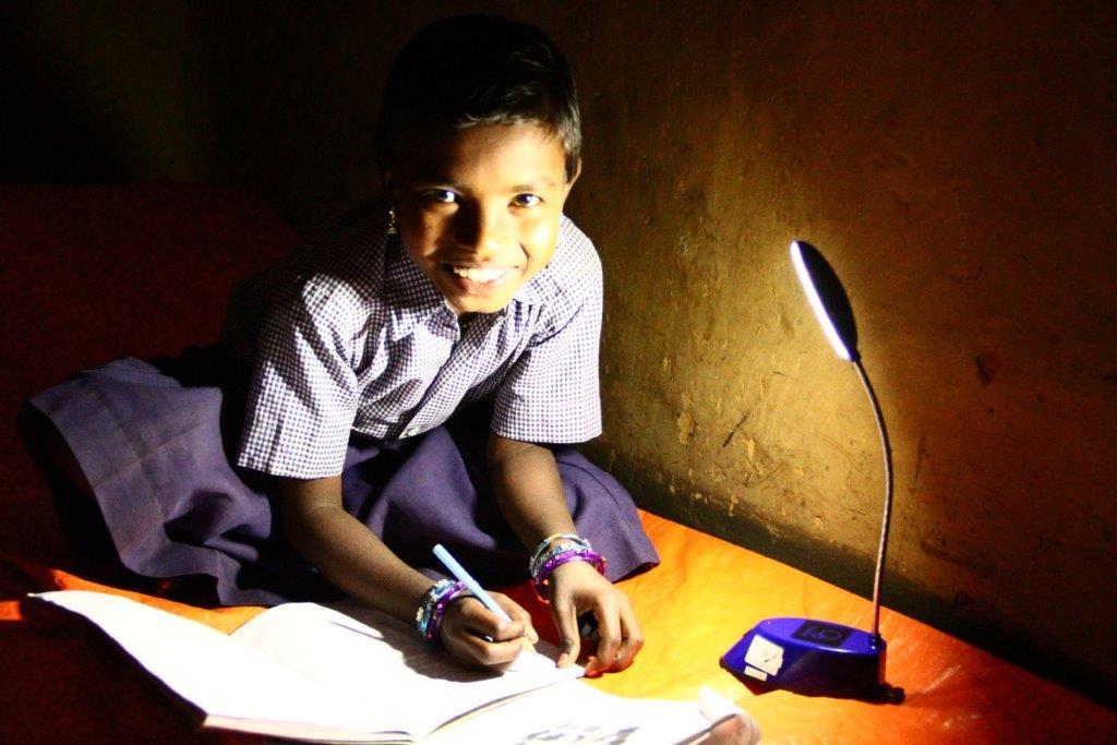 Ein Schulmädchen sitzt auf ihre Bett und macht im Schein einer LED-Lampe ihre Hausaufgaben.
