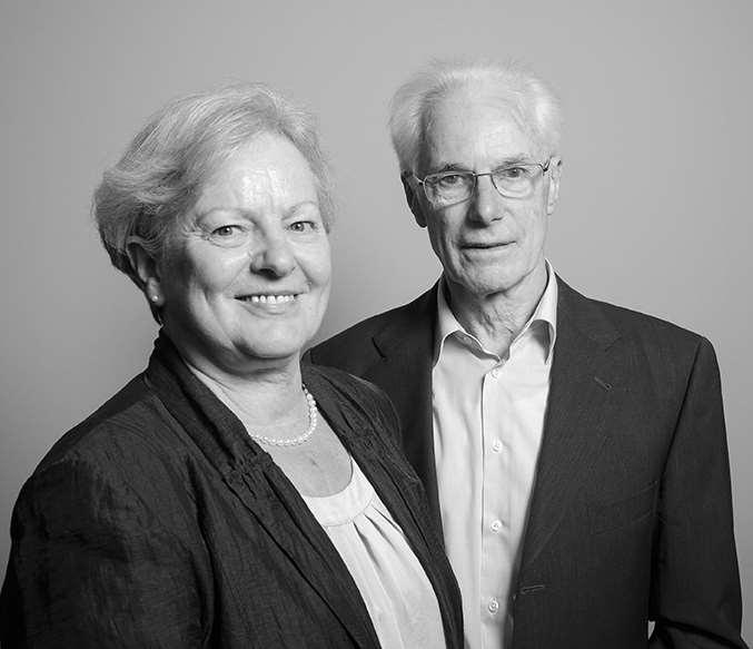 Ältere Frau mit offenem Lächeln steht im vorderen Bereich des Bildes und schaut in die Kamera. Ihr Mann steht versetzt hinter ihr und lächelt ebenfalls in die Kamera.