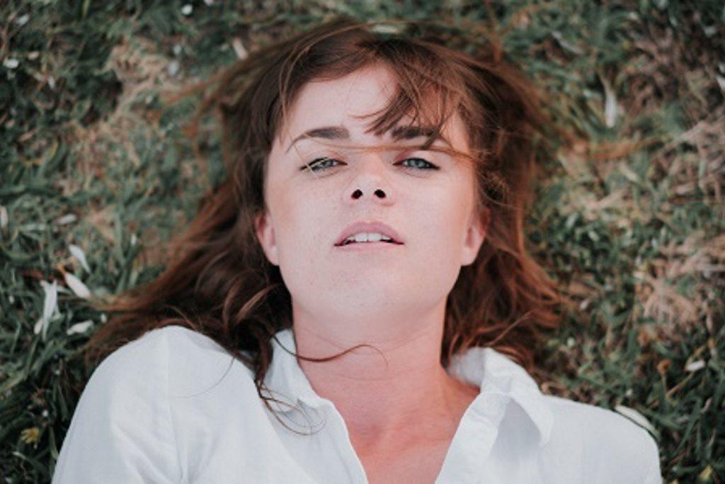Eine Frau mit rotbraunen Harre und weißer Bluse liegt auf einer Wiese und schaut direkt in die Kamera.