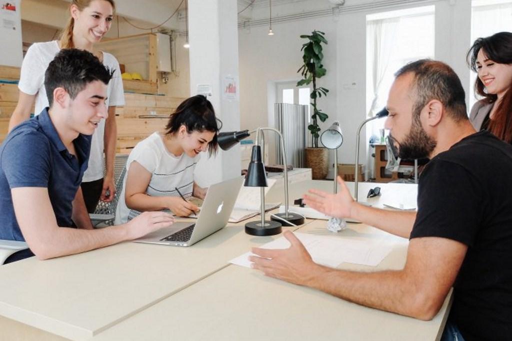 Eine Gruppe von Menschen aus unterschiedlichen Kulturen sitzt an einem Tisch und diskutiert.